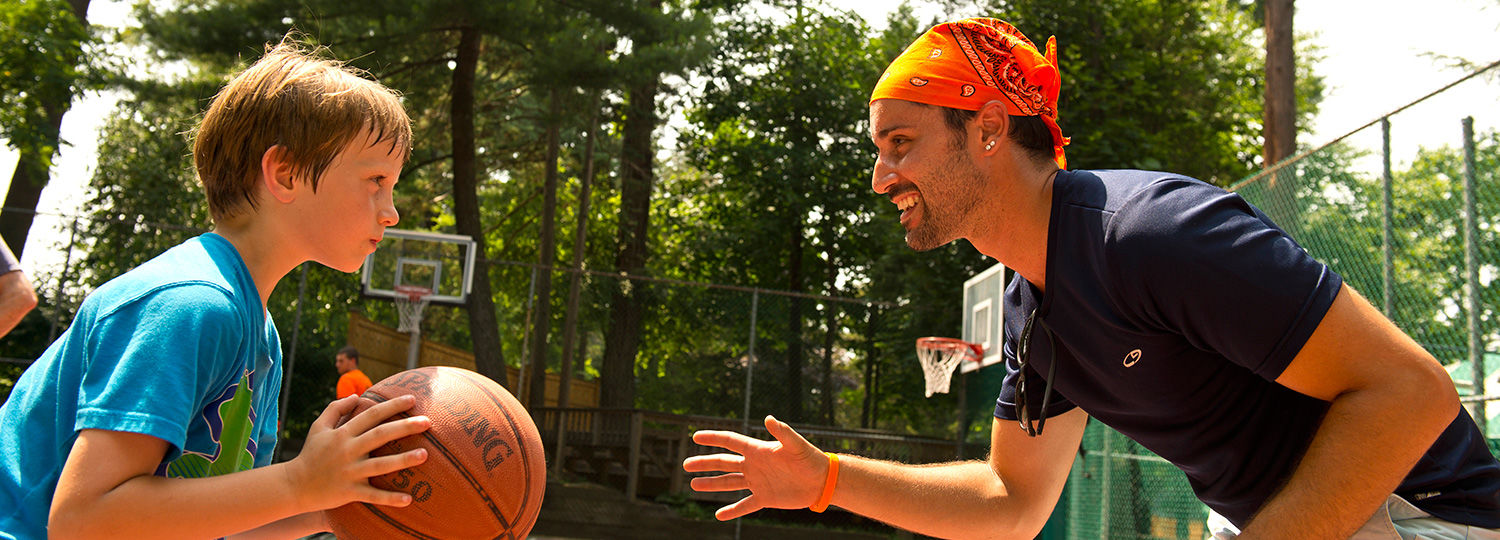 Counselor playing basketball with boy